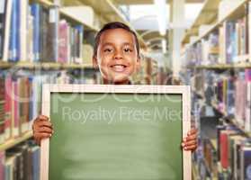 Smiling Hispanic Boy Holding Empty Chalk Board in Library