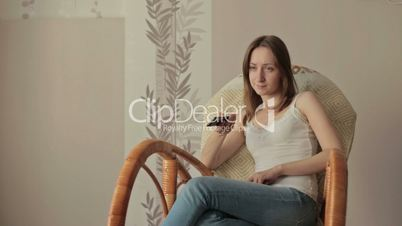 Girl on armchair, rocker with remote control