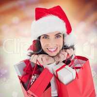 Composite image of smiling brunette holding shopping bags full o
