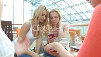 Women with smartphones at cafe