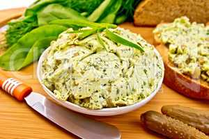 Butter with spinach and herbs in bowl on board
