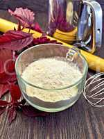 Flour amaranth in glass cup on board with rolling pin