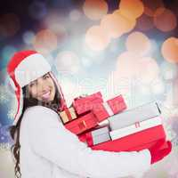 Composite image of festive brunette in winter clothes holding ma