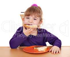 hungry little girl eats bread with chocolate cream