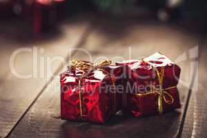 Christmas gift box with red ribbon on dark wooden background in vintage style