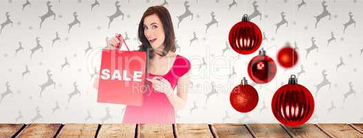 Composite image of stylish brunette in red dress showing sale ba