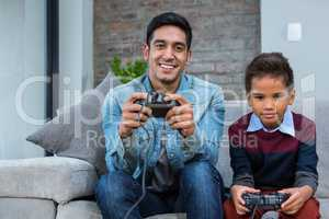 Happy father playing video games with his son