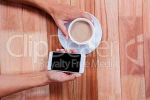Hands holding smartphone and coffee