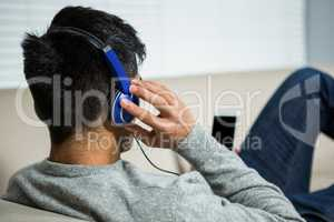 Over shoulder view of casual man listening music