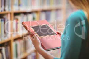 Over shoulder view of student in library holding book