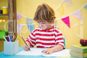 Boy using a pencil to write on paper