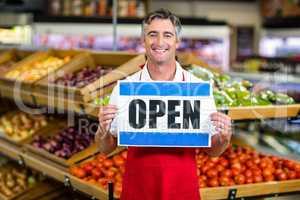 Smiling seller holding sign