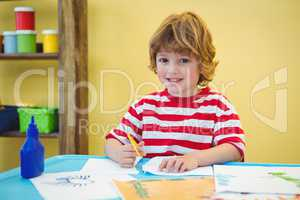 Boy using scissors to cut paper
