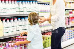 Mother and son looking at the supermarket fridge