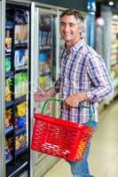 Smiling man opening supermarket fridge