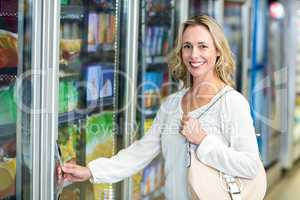 Smiling woman opening supermarket fridge