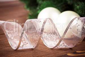 Christmas background with white ribbon and Christmas balls on wooden background