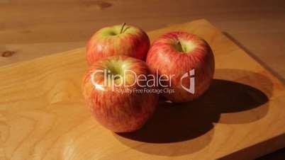 Three apples on a cutting board