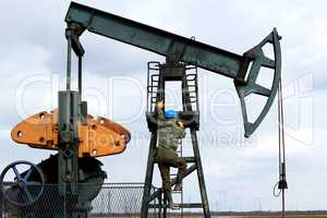 oil worker climbs to the pumpjack