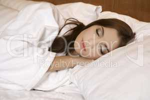 Closeup portrait of a cute young woman sleeping on the bed
