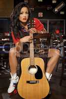 Young adult brunette woman with guitar