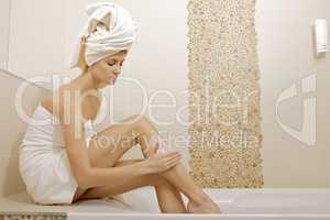 Woman applying moisturizer cream on the legs