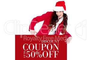 Composite image of festive brunette pointing white poster