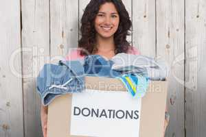 Composite image of volunteer holding clothes donation box