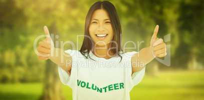 Composite image of woman wearing volunteer tshirt giving thumbs