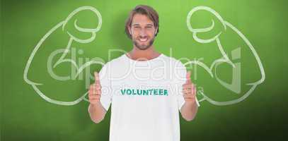 Composite image of happy man wearing volunteer tshirt giving thu