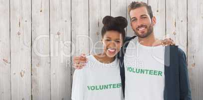 Composite image of portrait of two young volunteers with arms ar