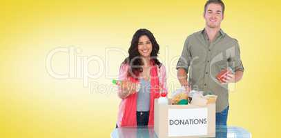 Composite image of smiling volunteers taking out food from donat