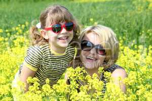 happy mother and daughter in yellow flowers field