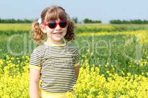 little girl posing in yellow flowers field