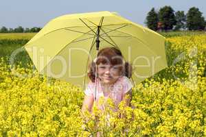 beautiful little girl with umbrella standing in yellow flowers f