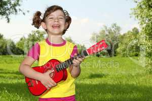 happy little girl play guitar in park