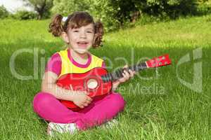 little girl sitting on grass play guitar and sing