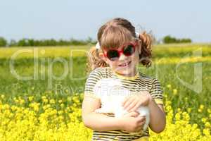 little girl with bunny pet in yellow field