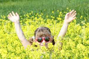 little girl with hands up in yellow flower field
