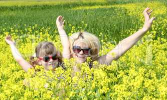 mother and daughter in yellow flower field