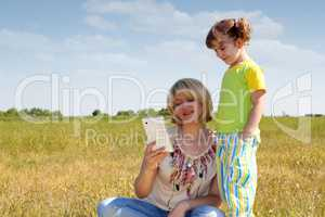 mother and daughter with tablet in field
