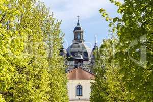 Baroque monastery through green trees
