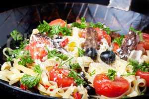 frische Pasta mit Tomaten und Oliven in einer Pfanne