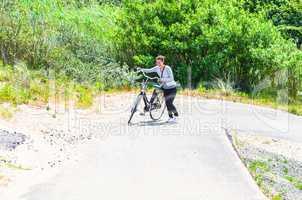 Junge Frau schieb ihr Fahrrad