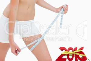 Composite image of close up of a slim woman measuring her thigh