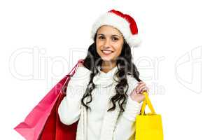 Smiling woman with christmas hat holding colored shopping bags