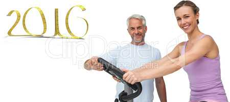 Composite image of portrait of a happy woman on stationary bike