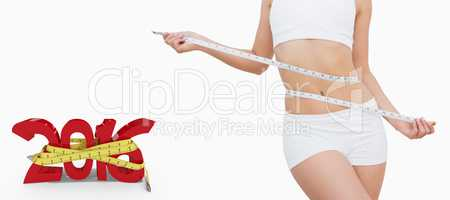 Composite image of slim woman measuring waist with tape measure