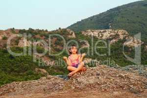 little girl sitting on a mountain top and meditate