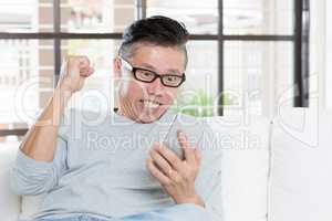 Mature Asian man celebrates success while using smartphone